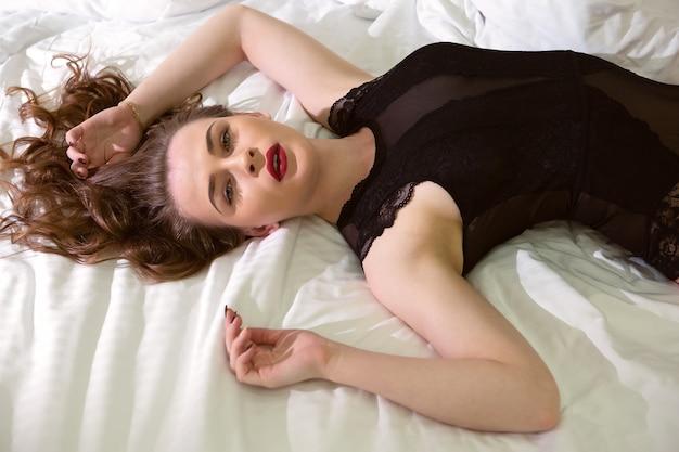 Une Belle Fille Aux Magnifiques Cheveux Noirs Est Allongée Sur Un Lit Redressé En Sous-vêtements Sexy Photo Premium