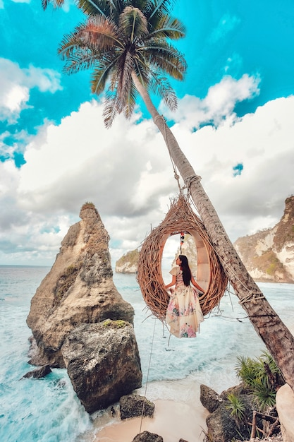 Belle Fille Sur Balançoires Cocotiers Sur La Plage De Daimond Beach, île De Nusa Penida à Bali, Indonésie Photo Premium