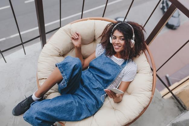 Belle Fille En Baskets Noires Se Trouve Dans Une Pose Confortable Sur Un Grand Oreiller Et Apprécie La Musique Photo gratuit