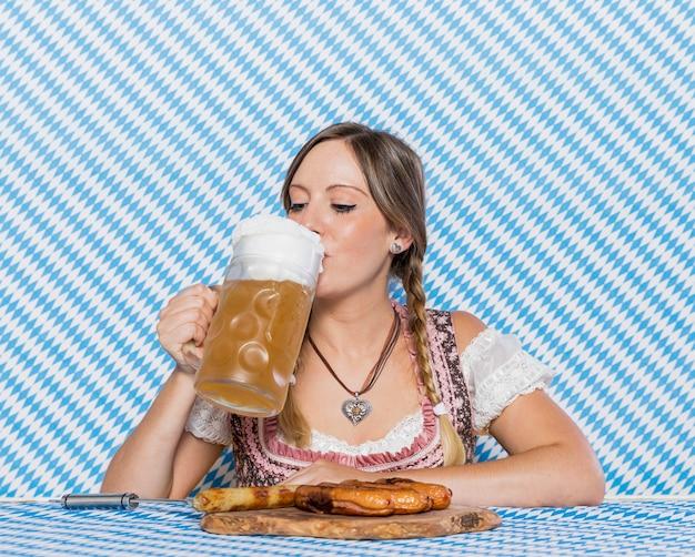 Belle Fille Bavaroise Buvant De La Bière Photo gratuit