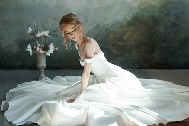 Belle fille blonde assise sur le sol en robe longue blanche. Photo Premium