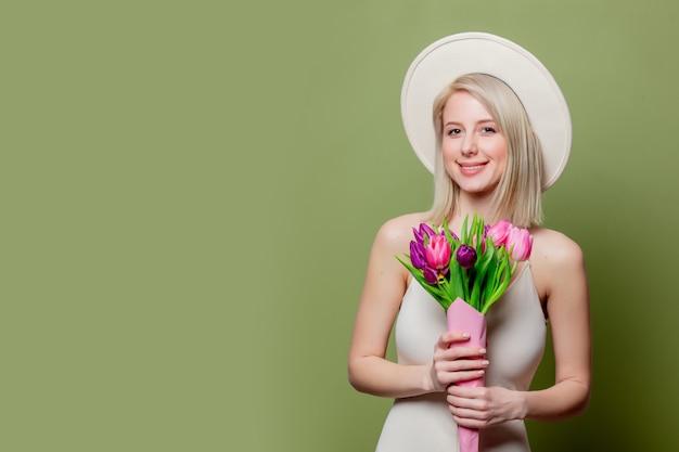 Belle Fille Blonde Au Chapeau Blanc Et Robe Avec Des Tulipes Photo Premium