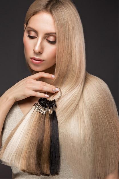 Belle Fille Blonde Aux Cheveux Parfaitement Lisses, Maquillage Classique Avec Une Palette Pour Les Extensions De Cheveux Dans Les Mains, Beauté Du Visage, Photo Premium