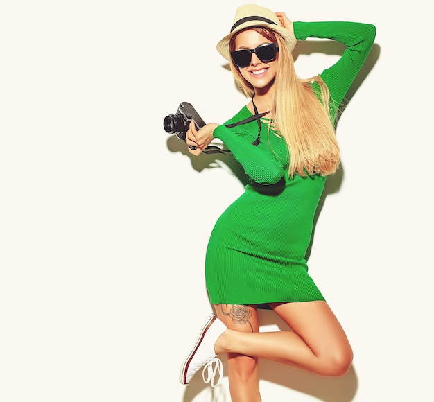 Belle Fille Blonde Mignonne Heureuse Dans Des Vêtements Décontractés De Hipster Vert D'été Prend Des Photos Tenant Un Appareil Photo Rétro Photo gratuit