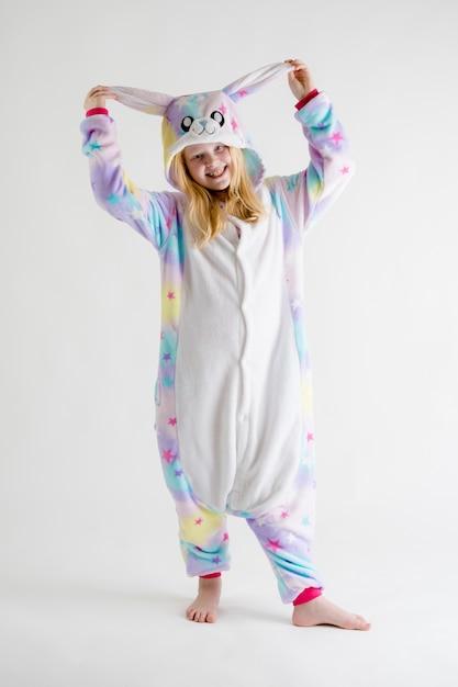 Belle fille blonde posant sur blanc en pyjama kigurumi, costume de lapin Photo Premium