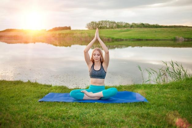 Belle Fille Blonde Sportive Pratiquant Le Yoga Sur Le Lac Au Coucher Du Soleil, Gros Plan, Elle Favorise Une Vie Saine Photo Premium