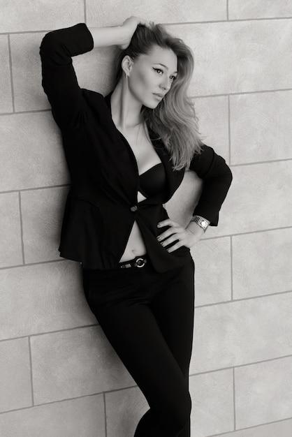 La belle fille la blonde en tenue classique. la jeune fille à la mode Photo Premium