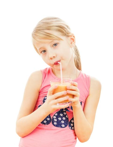 Belle fille boit des smoothies au pamplemousse isolés sur blanc. Photo Premium