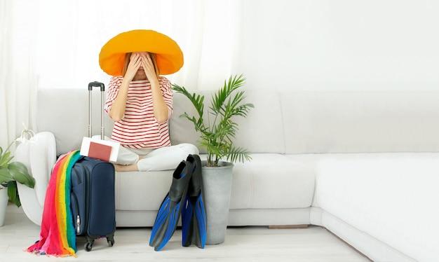 Belle Fille Bouleversée Dans Un Chapeau Jaune Reste à La Maison Et Prévoit Un Voyage En Vacances. En Attente De Voyage. Photo Premium