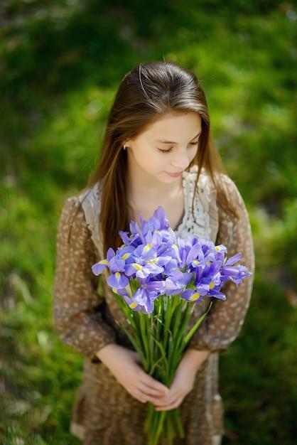 Belle Fille Avec Un Bouquet D'iris Violet Violet Dans Ses Mains Photo Premium
