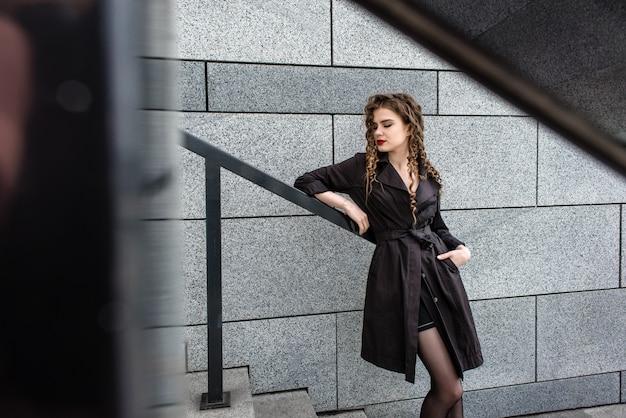 Belle fille brune à la mode dans une ville moderne Photo Premium