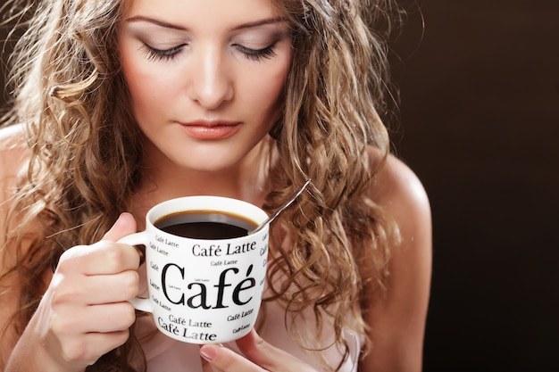 Belle fille buvant du thé ou du café. Photo Premium