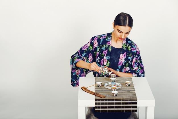 Belle fille buvant un thé dans un studio Photo gratuit