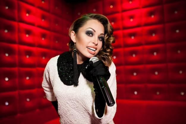Belle fille chante au karaoké dans une discothèque Photo Premium