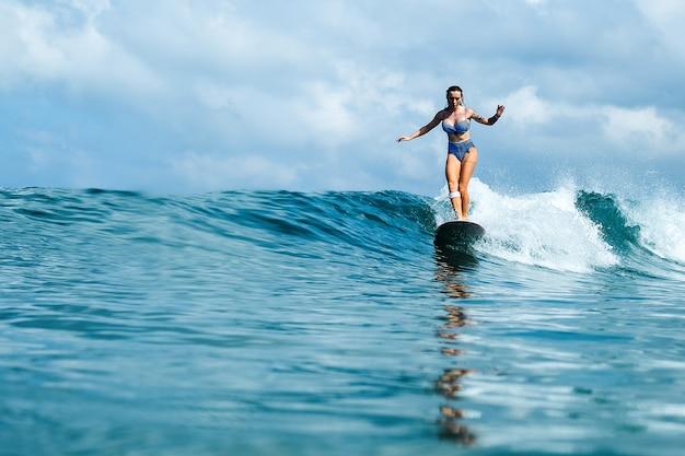 Belle fille à cheval sur une planche de surf sur les vagues Photo gratuit