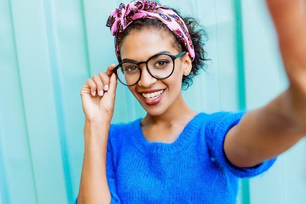 Belle Fille Avec Une Coiffure élégante Faisant Autoportrait Par Caméra Sur Turquoise Photo gratuit