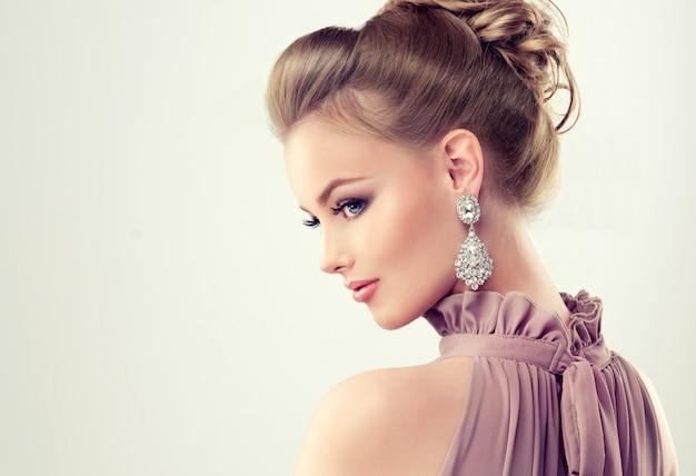 Belle fille avec une coiffure élégante et de grosses boucles d'oreilles Photo Premium