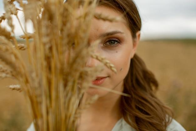 Une Belle Fille A Couvert La Moitié De Son Visage Avec Un Bouquet D'oreilles. Photo Premium