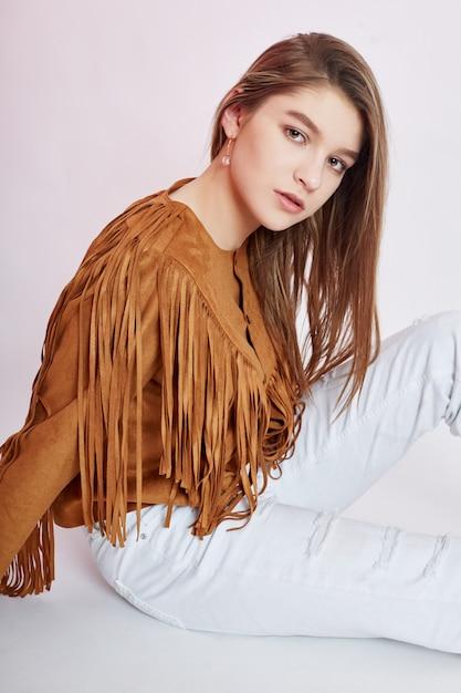 Belle fille de cow-boy en jeans blancs sur fond blanc. jeune adolescente Photo Premium