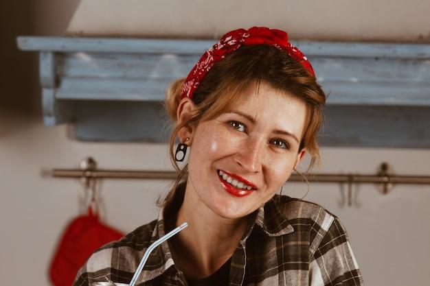 Belle Fille Dans Un Bandana Boit Du Coca-cola à Travers Une Paille, Sourit, Lèvres Rouges, S'assoit à La Maison Dans La Cuisine. Publicité, Concept De Nouvel An. Photo De Pin-up. Photo Premium