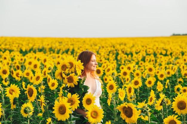 Belle fille dans un immense champ jaune de tournesols. Photo Premium