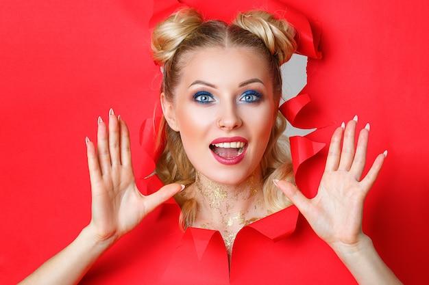 Une belle fille dans des montées d'un trou en papier rouge Photo Premium