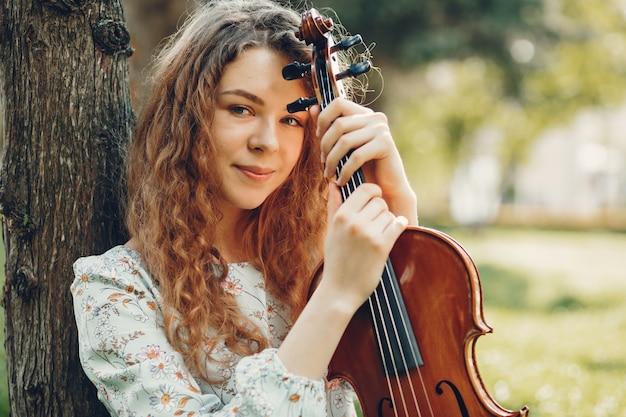 Belle fille dans un parc d'été avec un violon Photo gratuit