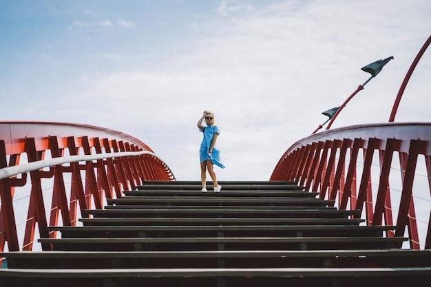 Belle fille dans une robe bleue posant sur le pont Photo gratuit