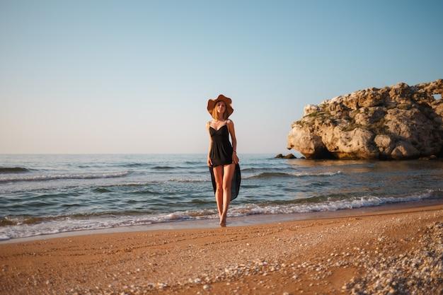 Belle fille dans une robe noire et un chapeau se promène le long du rivage de sable de la mer au coucher du soleil Photo Premium