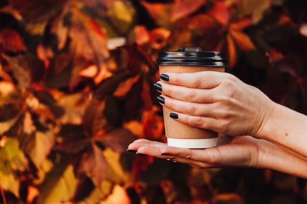 Belle fille dans la rue automne tient une tasse avec une boisson chaude dans ses mains Photo Premium