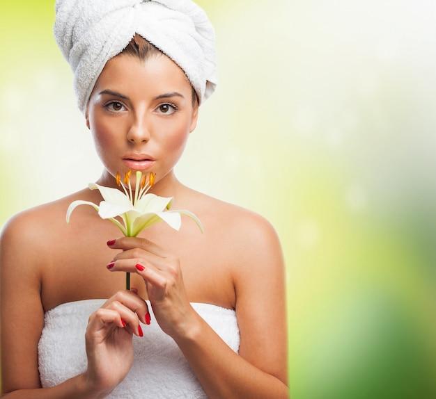 Belle fille dans une serviette tenant lys blanc Photo gratuit
