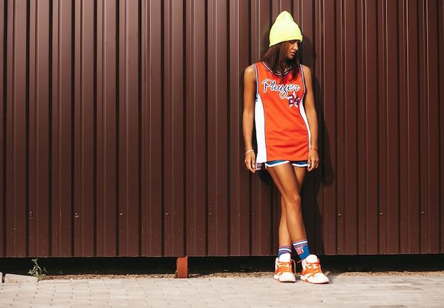 Belle Fille Dans Les Sports De Basket-ball Rouge Posant Près D'un Mur Métallique Marron Photo gratuit