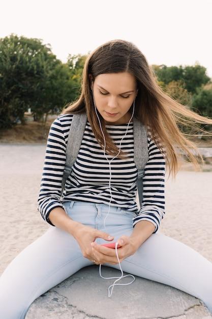 Belle fille dans un t-shirt rayé, écouter de la musique sur la plage Photo Premium
