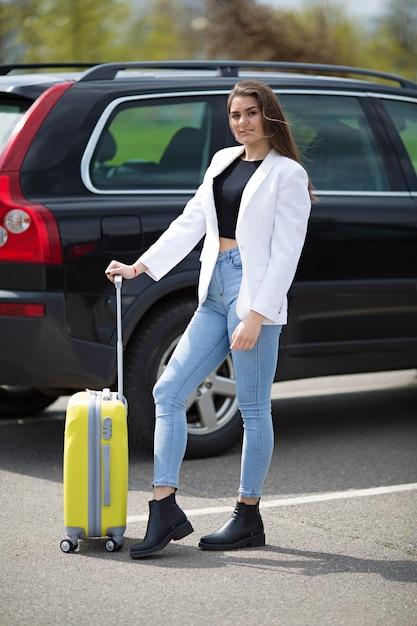Belle fille dans une veste blanche se dresse avec une grande valise jaune Photo Premium