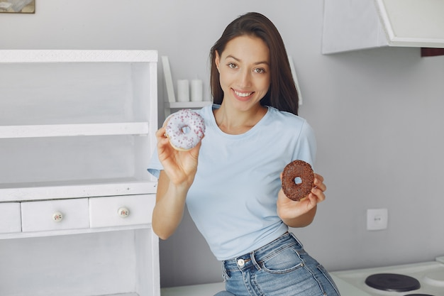 Belle fille debout dans une cuisine avec beignet Photo gratuit