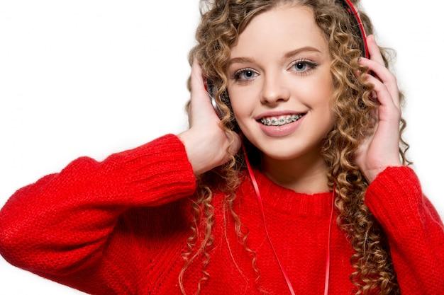 Belle Fille, écouter De La Musique Dans Les écouteurs Rouges. Isoler. Portrait D'une Jeune Fille Avec Appareil Orthodontique. Photo Premium