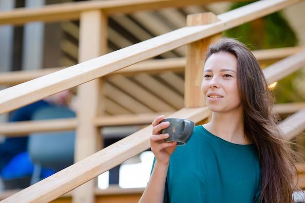 Belle fille élégante prenant son petit déjeuner au café en plein air Photo Premium