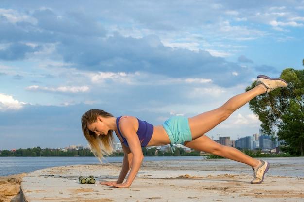 La belle fille avec une figure sportive fait du fitness en plein air près du lac. Photo Premium