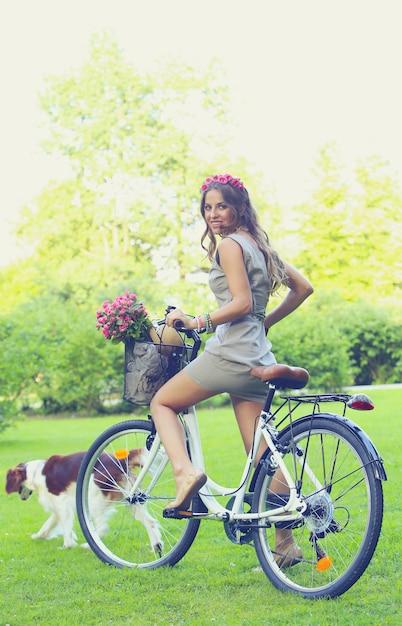 Belle fille avec des fleurs sur un vélo Photo gratuit