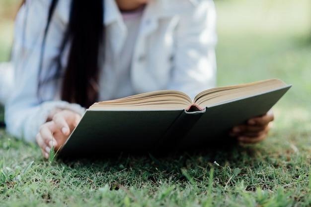 Belle fille en forêt d'automne en lisant un livre Photo gratuit