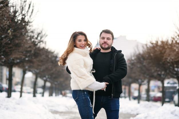 Belle Fille Heureuse Et Son Beau Petit Ami Marchons Ensemble Dans La Rue Enneigée De L'hiver. Nouvel An Et Noël. Photo Premium