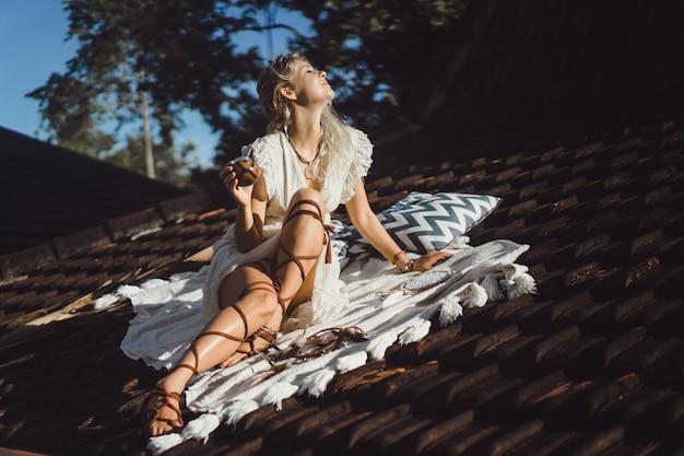 Belle fille hippie indienne aux longs cheveux blonds sur le toit, buvant du thé de son compagnon. Photo gratuit