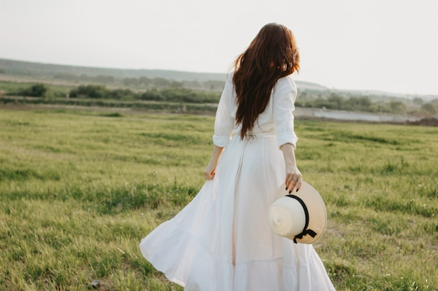 Belle fille insouciante cheveux longs en vêtements blancs et chapeau de paille profite de la vie dans la nature sur le terrain au coucher du soleil Photo Premium