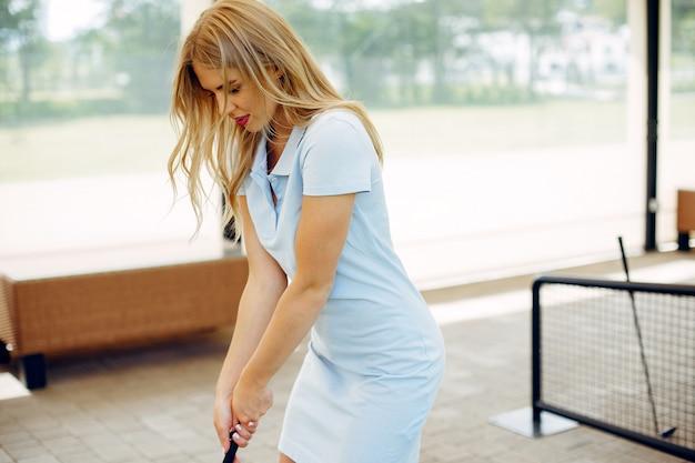 Belle fille jouant au golf sur un parcours de golf Photo gratuit