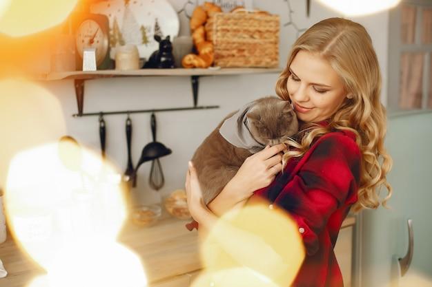 Belle fille jouant avec un chat à la maison Photo gratuit