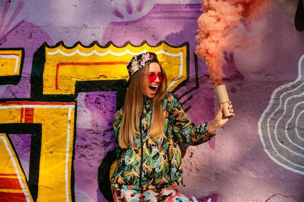 Belle fille joyeuse dans des vêtements élégants colorés avec fusée de fumée, s'amuser le temps Photo gratuit