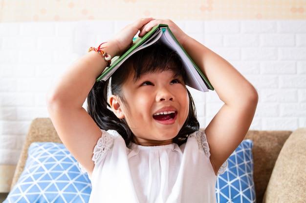Belle Fille Joyeuse Avec Un Livre Sur La Tête Photo gratuit