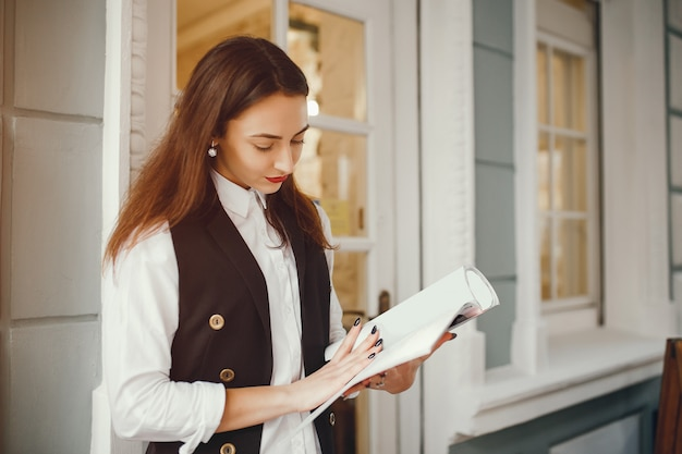 Une belle fille lit un magazine dans un café Photo gratuit