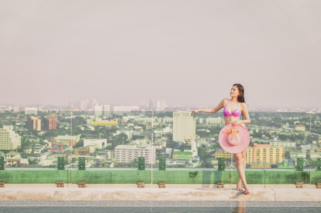 Belle fille en maillot de bain est relaxant à la piscine. Photo Premium