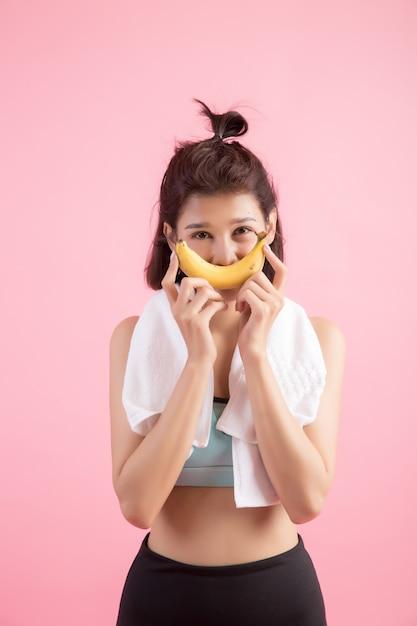 Belle fille mange des bananes après l'effort pour contrôler son poids Photo gratuit